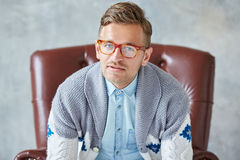 Portrait of a young intelligent man stares into the camera, good. View, small unshaven, charismatic, wearing glasses rimmed with brown, blue shirt, gray sweater Stock Photo