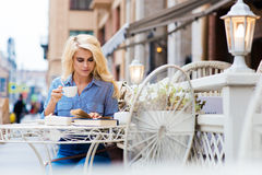 Portrait of a young intelligent woman enjoying coffee during read book while sitting in restaurant in the fresh air, Stock Photos