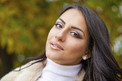 Portrait of young Italians in beige coat. Against the background of the autumn park Stock Photography