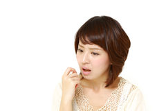 Portrait of young Japanese woman worries about something. Studio shot of young Japanese woman on white background stock image