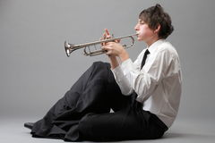Portrait of a young man playing his Trumpet. Portrait of a young jazz man playing his Trumpet grey background Royalty Free Stock Photos