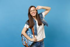 Portrait of young joyful funny smart woman student in white t-shirt, denim clothes with backpack holding glasses stand