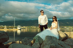 Portrait of young just married couple in wedding gowns and stylish sunglasses on the rock at the seaside. Mountains on background. Wedding fashion and eyewear Stock Photos