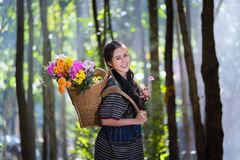 Portrait young karen women smiled hand hole flower and flower ba. Portrait young karen woman smiled hand hole flower and flower basket on black in the forest royalty free stock image