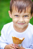 Portrait of young kid eating a tasty ice cream. Stock Images