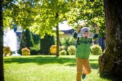 Portrait of young kid running and smiling in the park stock photo