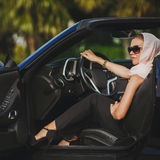Portrait of a young lady in a black convertible. Young lady brunette with long hair, wearing sun glasses, wearing earrings, wearing a black summer dress royalty free stock image