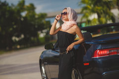 Portrait of a young lady in a black convertible. Young lady brunette with long hair, wearing sun glasses, wearing earrings, wearing a black summer dress stock image