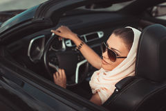 Portrait of a young lady in a black convertible. Stock Images