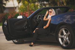 Portrait of a young lady in a black convertible. Royalty Free Stock Photo