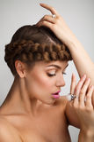 Portrait of a young lady with a braid. On grey background Royalty Free Stock Images