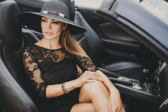 Portrait of a young lady in the car in a big black hat. Royalty Free Stock Photo