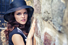 Portrait of young lady in hat near stone wall Royalty Free Stock Photos