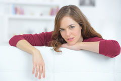 Portrait young lady leaning over back sofa Stock Image