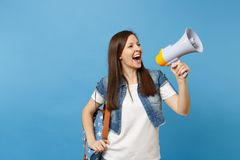 Portrait of young laughing beautiful woman student in denim clothes with backpack make announcement with megaphone. Isolated on blue background. Education in stock photos