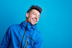 Portrait of a young laughing man in a studio with anorak on a blue background. Copy space royalty free stock photography
