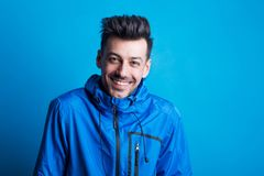 Portrait of a young laughing man in a studio with anorak on a blue background. Portrait of a young laughing man in a studio with blue anorak on a blue stock photography