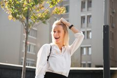Portrait of young laughing woman in modern clothes fooling around trying on new look. royalty free stock image