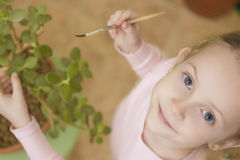 Portrait of young little girl cleaning flower's leafs Royalty Free Stock Image