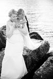 Portrait of a young little girl embracing her mother on the sea Stock Image