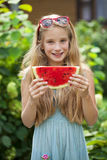 Portrait of a young little girl with watermelon. Portrait of a young blonde little girl with watermelon, summer outdoor Royalty Free Stock Photos
