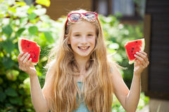 Portrait of a young little girl with watermelon. Portrait of a young blonde little girl with watermelon, summer outdoor Royalty Free Stock Images