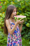 Portrait of a young little girl with watermelon. Portrait of a young brunette little girl with watermelon, summer outdoor Royalty Free Stock Photography