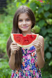 Portrait of a young little girl with watermelon. Portrait of a young brunette little girl with watermelon, summer outdoor Royalty Free Stock Images