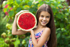 Portrait of a young little girl with watermelon. Portrait of a young brunette little girl with watermelon, summer outdoor Royalty Free Stock Photos