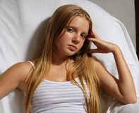 Portrait of young long-haired. Model sitting in an arm-chair Stock Photography