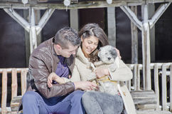 Portrait of a young love couple and their dog. Portrait of a young love couple hugging their dog in the winter mountain Stock Images