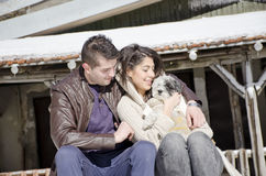 Portrait of a young love couple and their dog. Portrait of a young love couple hugging their dog in the winter mountain Stock Photography