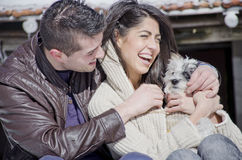 Portrait of a young love couple and their dog. Portrait of a young love couple hugging their dog in the winter mountain Royalty Free Stock Images