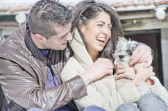 Portrait of a young love couple and their dog. Portrait of a young love couple hugging their dog in the winter mountain Stock Photo