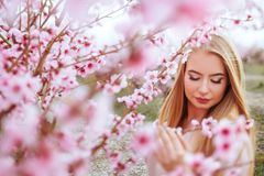 Portrait of young lovely woman in spring flowers royalty free stock images