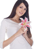 Portrait of young lovely brunette with flower in hands Stock Image