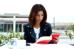 Portrait of young lovely female enjoying a good book while sitting at the table in coffee shop terrace royalty free stock images