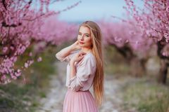 Portrait of young lovely woman in spring flowers stock image