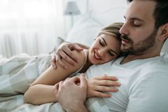 Portrait of young loving couple in bedroom Stock Images
