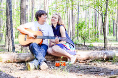 Portrait of young loving happy couple with guitar in forest. stock photos