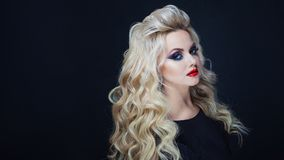 Portrait of a young luxurious blonde with long curls. Bright makeup for party, dark background royalty free stock image
