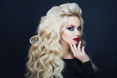 Portrait of a young luxurious blonde with long curls. Bright makeup for party, dark background stock photos