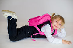 Portrait of young lying schoolgirl with schoolbag. Portrait of young lying schoolgirl with pink schoolbag.  on white background Stock Photo