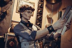 Portrait of a young mad scientist traveler in a steampunk style. Suit with a card in the background of scenery with gears royalty free stock images