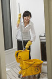 Portrait of young maidservant with mop royalty free stock photography