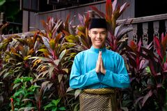 A portrait of young malay man in his traditional teal cloth, samping songket and songkok. Selamat Hari Raya gesture