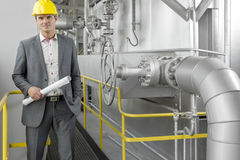 Portrait of young male architect holding blueprint by machinery at industry Stock Photography