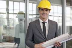 Portrait of young male architect holding rolled up blueprints in industry Royalty Free Stock Images