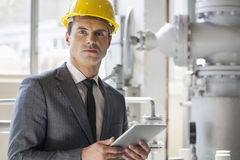 Portrait of young male architect holding tablet computer in industry stock images
