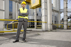 Portrait of young male architect standing arms crossed outside industry Royalty Free Stock Image